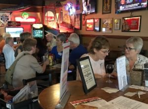 Members socializing at the bar surrounded by League promotional materials
